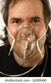 A male breathing through an oxygen mask with odd expression on his face.