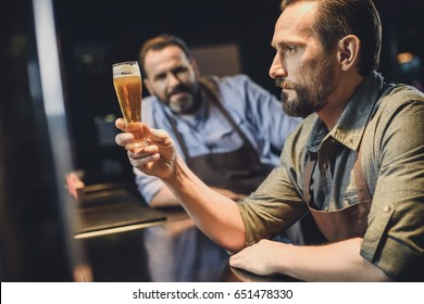 Male brewery worker examining small glass of beer