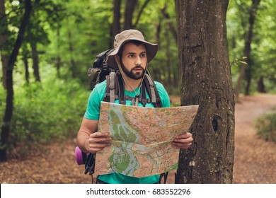 Male brunet bearded confused tourist got lost in the forest, holding map, looking far, trying to find the way. He has a backpack, all needed for overnight stay. Search the trail way