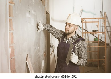 Male builder is checking the quality of the work done after the plaster wall at home.
