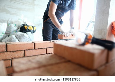 Male builder hand in gloves holding clay brick on background of brickwork wall. Repair and redevelopment apartments concept.