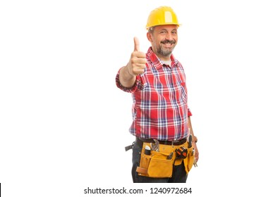 Male builder holding thumb up as like gesture wearing yellow hardhat and toolbelt isolated on white background