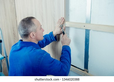 male builder revets wood panels for a facade of walls
