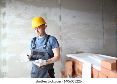 Male builder in yellow hard hat holds clipboard on background of an apartment under repair portrait. Estimated property value concept.