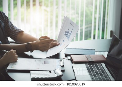 A male business consultant describes a marketing plan to set business strategies for women business owners witch using notebook.