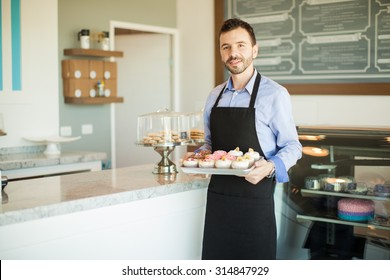 Male business owner in an apron holding a tray of cupcakes and standing in front of his bakery