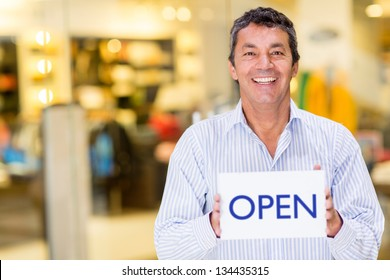 Male business owner holding an open sign and smiling