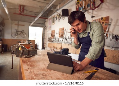 Male Business Owner In Workshop Using Digital Tablet And Making Call On Mobile Phone - Shutterstock ID 1721678116