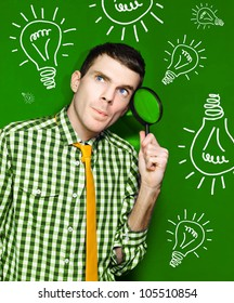 Male Business Person Thinking With Spy Glass To Face In Front Of A Green Light Bulb Background In A Portrayal Of Discovery And Creative Ideas