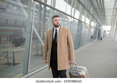 Male businessman, with a beard, in a black jacket and coat, on the background of a large modern business center made of glass