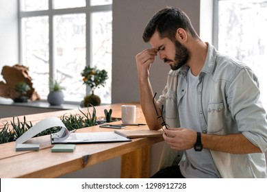 Male businessman concentrates on documents in office. Pensive manager trying to find solution for job problem with glasses in hands on his workplace near window