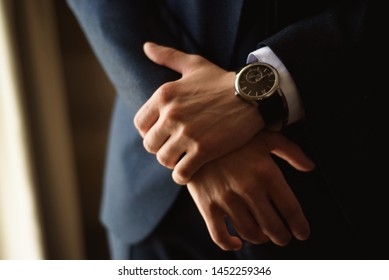 Male businessman dresses and adjusts his watch, preparing for a meeting. Clock.