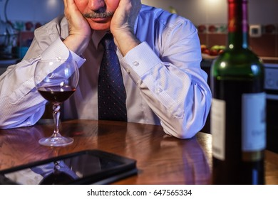 Male businessman drinking after  wine working day, trying to forget about problems
