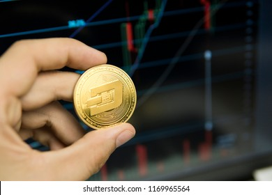 Male businessman hand holding Dash coin on a background of growth graph on a screen of laptop. Virtual money and Financial growth concept on chart background. Trading Mining of Dash coins.