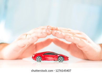 Male businessman hands above the small red miniature car. Car insurance concept.