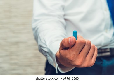 Male businessman holds blue pill. Looks like giving it to you.