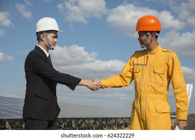 A male businessman shakes hands with a young engineer at power plant with a blue sky and white clouds