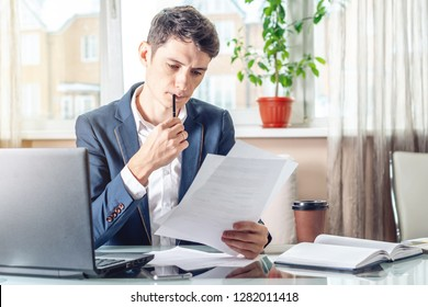 Male businessman sitting at a work place examing documents. The concept of the office working with documents