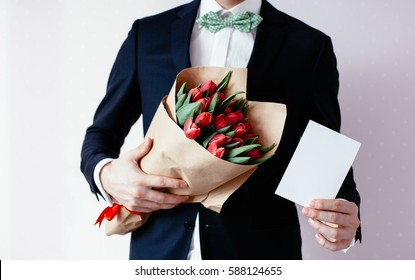 Male businessman in stylish suit holding a blank greeting card and bouquet of red tulips beautiful. Congratulations on the Day of Women, March 8, International Day Mom