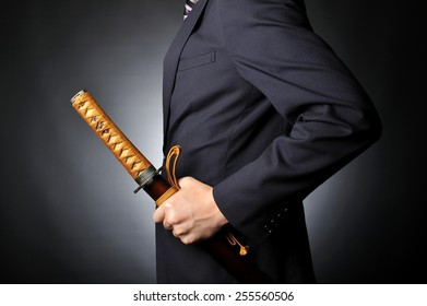 Male businessman wearing a suit to have the sword of Japanese samurai