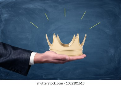 A male businessman's hand holding a golden crown on an open palm. Invitation to fist class. Join privileged group. Fame and success.