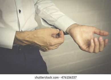 Male buttons cufflinks. Businessman buttons cufflinks in white shirt.