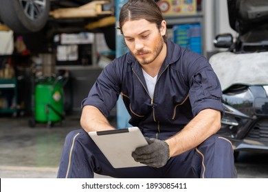 Male car mechanic worker working at auto repair shop. Male mechanic vehicle service using tablet in the garage. Auto car repair service, maintenance concept