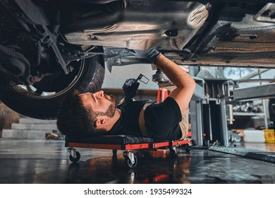 Male car mechanic worker working using wrench tool for repair, maintenance underneath car. Mechanic vehicle service checking under car in garage. Auto car repair service, maintenance concept.