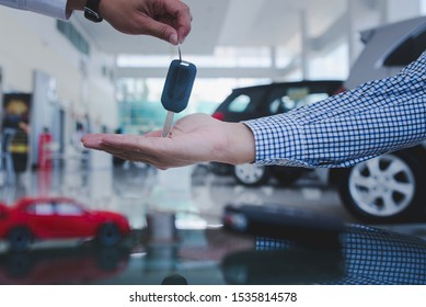 Male car salesman is going to give a new car key to an Asian business customer and sign a car dealer contract to buy a new car loan, trade money or investment.