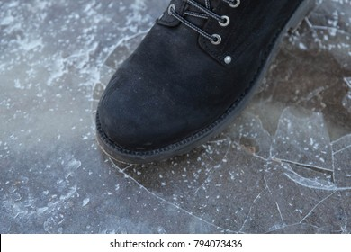 A male carefully walking on the slippery road - frozen puddle covered with ice, close up view of legs in black shoes and jeans. Danger concept.