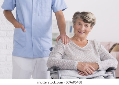 Male caregiver standing behind the woman on wheelchair with a hand on her shoulder