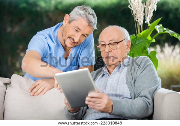 Male caretaker assisting senior man in using digital tablet at nursing home porch