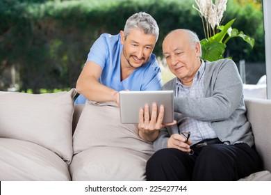 Male caretaker and senior man using tablet PC at nursing home porch