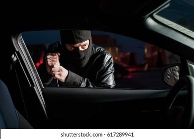 Male carjacker open car door with screwdriver