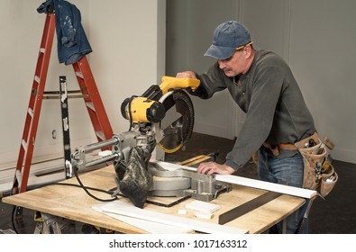 male carpenter cutting wood board with professional electric chop saw on work table on construction site during home remodeling, ladder in background