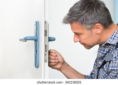 Male carpenter fixing lock in door with screwdriver at home