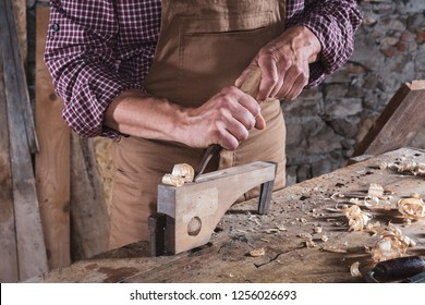 Male carpenter scraping curls off piece of wood sitting on work table covered in scraps using metal tool