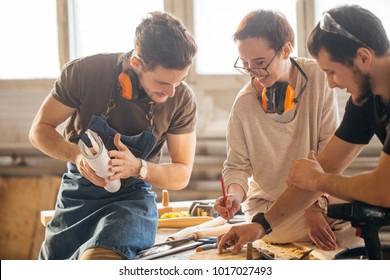 male Carpenter Training Female Apprentice To Use Plane