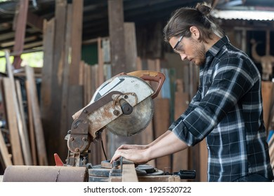 Male carpenter using circular saw cutting piece of wood and wearing safety goggles at woodwork workshop. Male woodworker working at work. Professional male craftsman