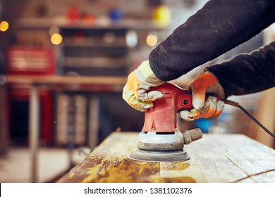 Male carpenter using orbital electric sander in a retro vintage workshop.