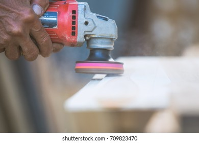 Male carpenter working with electric tools on wooden plank in workshop