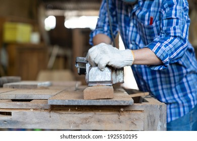 Male carpenter working with electric wood planer on wood lath on desk at woodwork workshop. Male craftsman