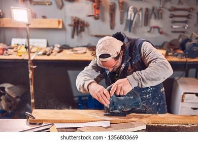 Male carpenter working on old wood in a retro vintage workshop.