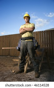 Male Caucasian construction worker stands confidently and looks into the camera. His arms are folded across his chest and a workbench can be seen behind him. Vertical shot.