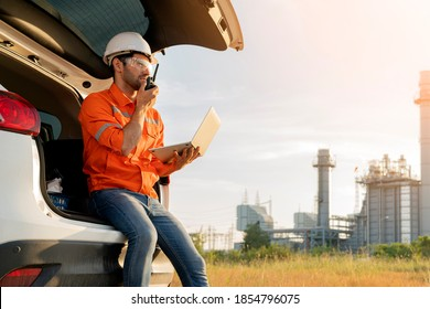 male caucasian engineer technician Industrial workers wearing safty uniform with walkie-talkie and laptop working inspection in a car with power plant background