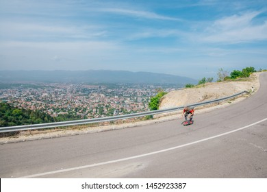Male Caucasian longboarder riding downhill on an empty road doing a speed tuck and grabbing the board while driving the longboard fast. Wearing a red t-shirt green hat and black jeans.