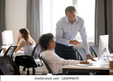 Male caucasian mentor explaining female african intern online task teaching new employee to work with corporate software, white executive boss helping black worker with computer project in office