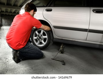 A male changing a tire on a car in a garage