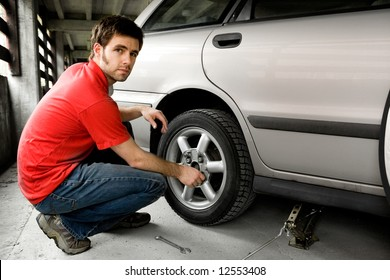 A male chaning a tire on a car