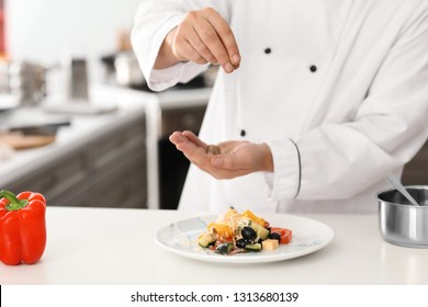 Male chef adding spices to tasty salad in kitchen, closeup